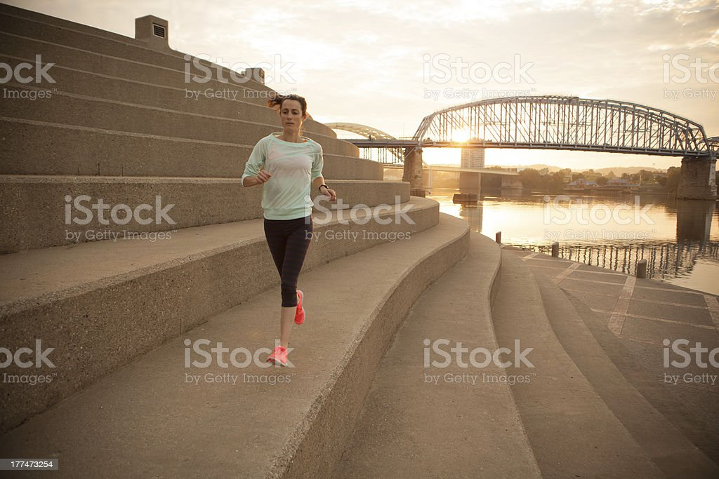 Woman running at sunset along Ohio River in Cincinnati stock photo