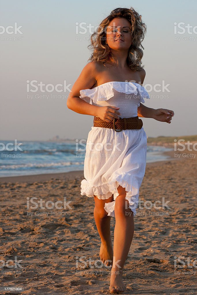 Woman running at the beach in white dress royalty-free stock photo
