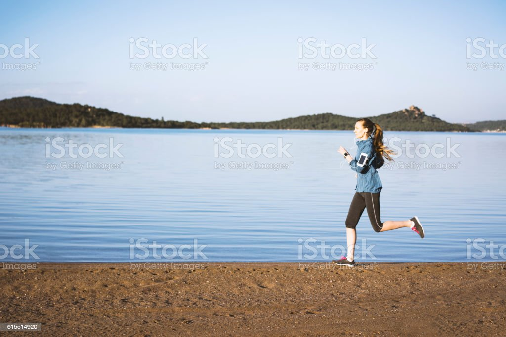 Woman running by the seashore stock photo