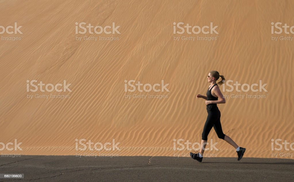 woman running in a Liwa desert stock photo