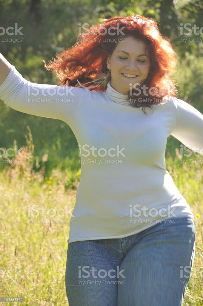 Woman running in a meadow stock photo