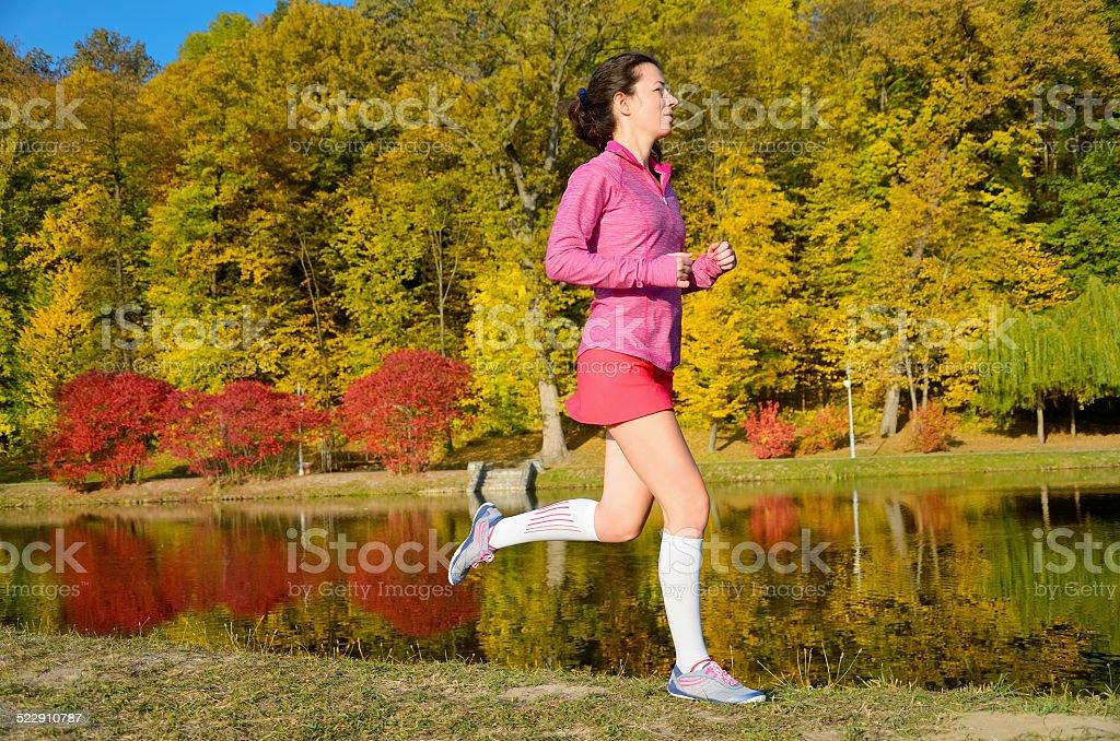 Woman running in autumn park, beautiful girl runner jogging stock photo