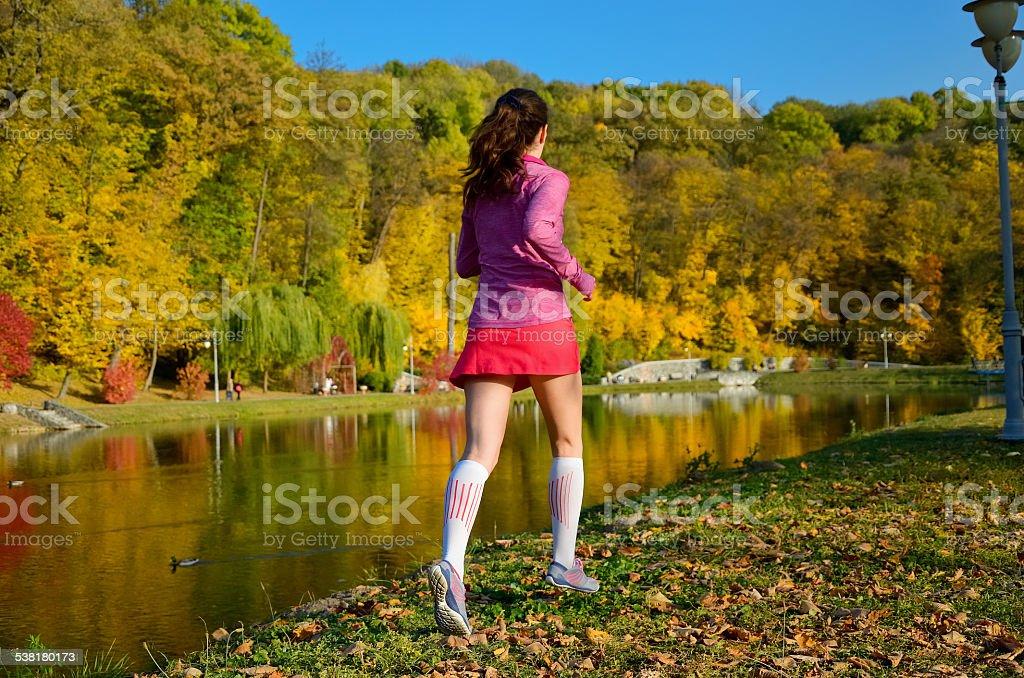 Woman running in autumn park stock photo