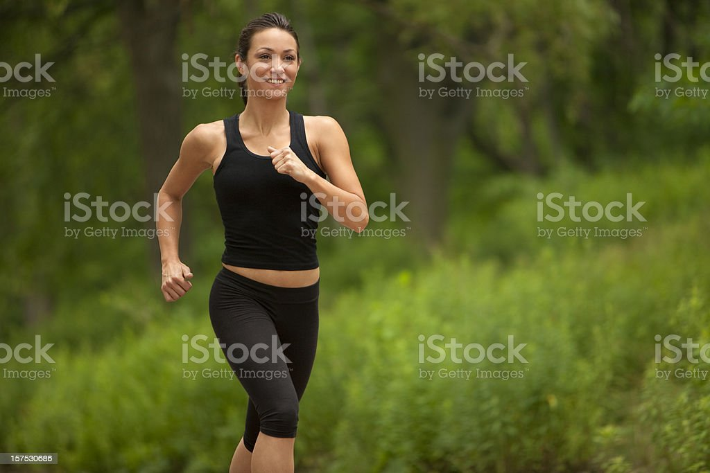 A woman running in black workout outfit stock photo