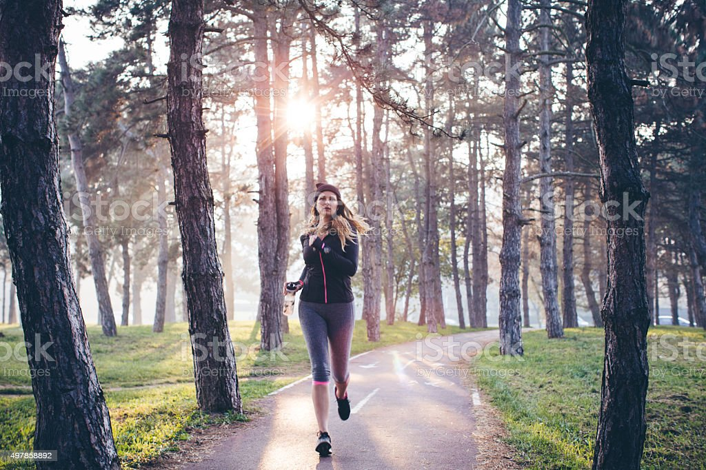Woman running in forest stock photo