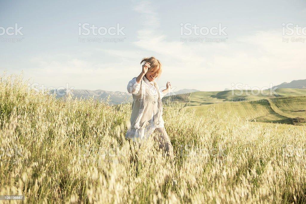 Woman running in grassy field stock photo