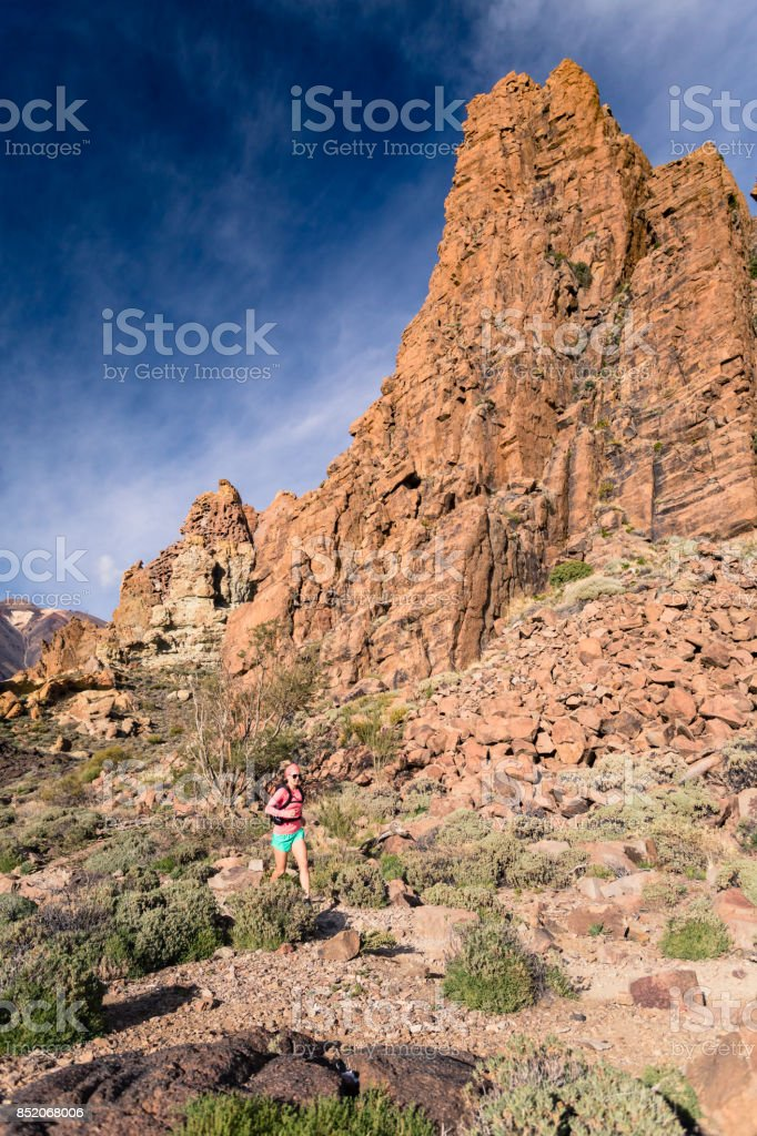 Woman running in mountains on rocky trail stock photo