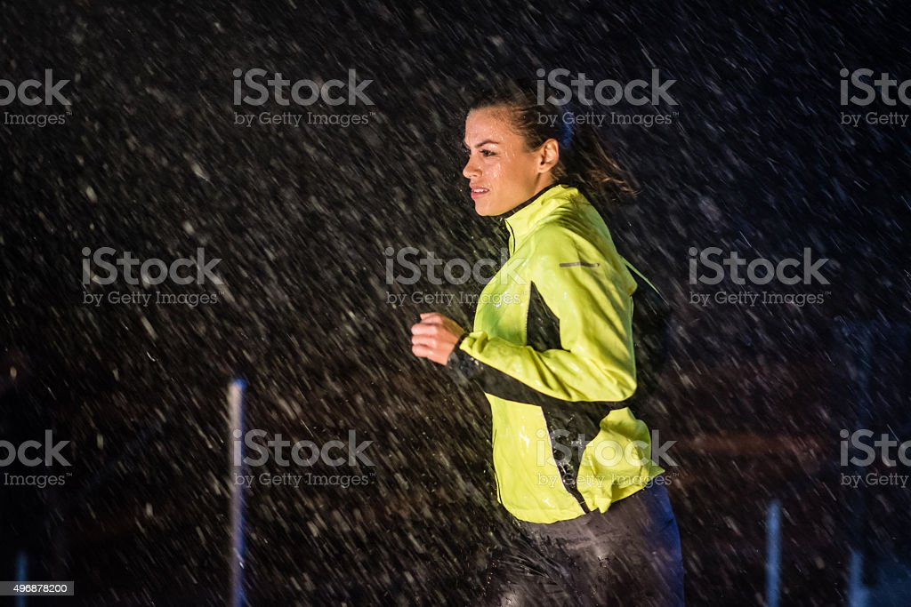 Woman running in rain stock photo