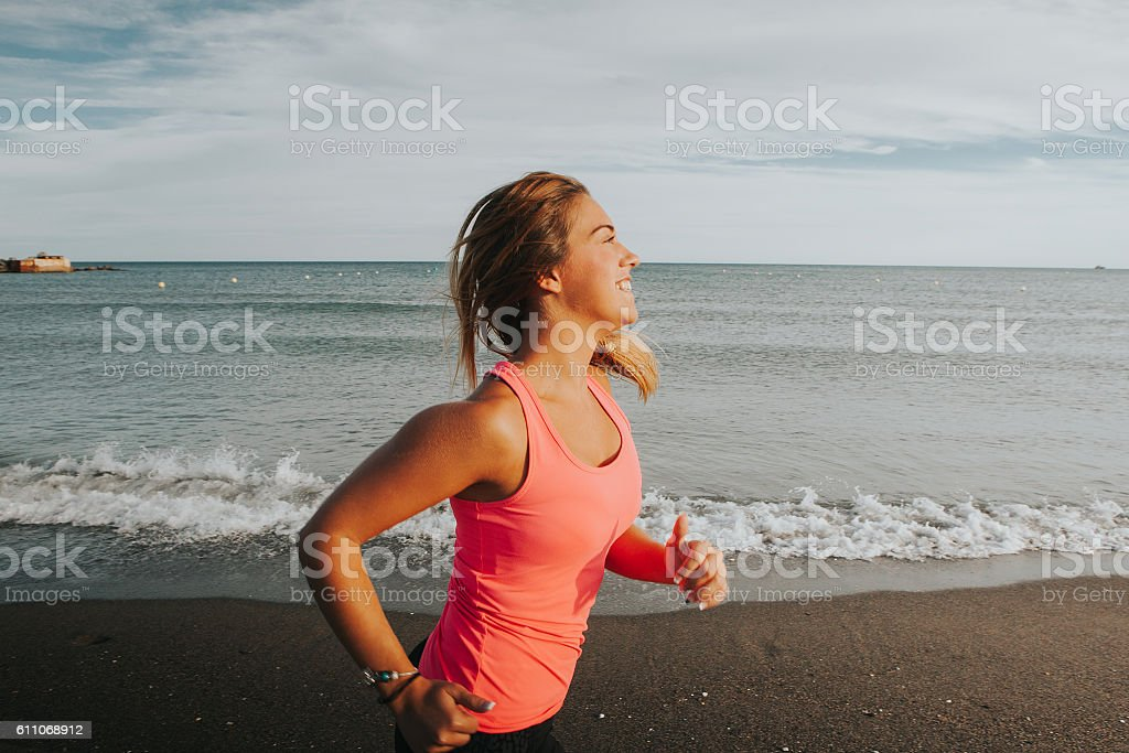 Woman running in the beach close to the water. stock photo