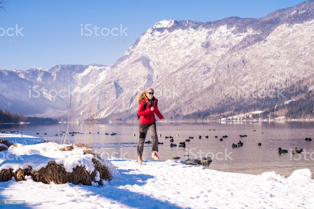 Woman running in the mountains stock photo