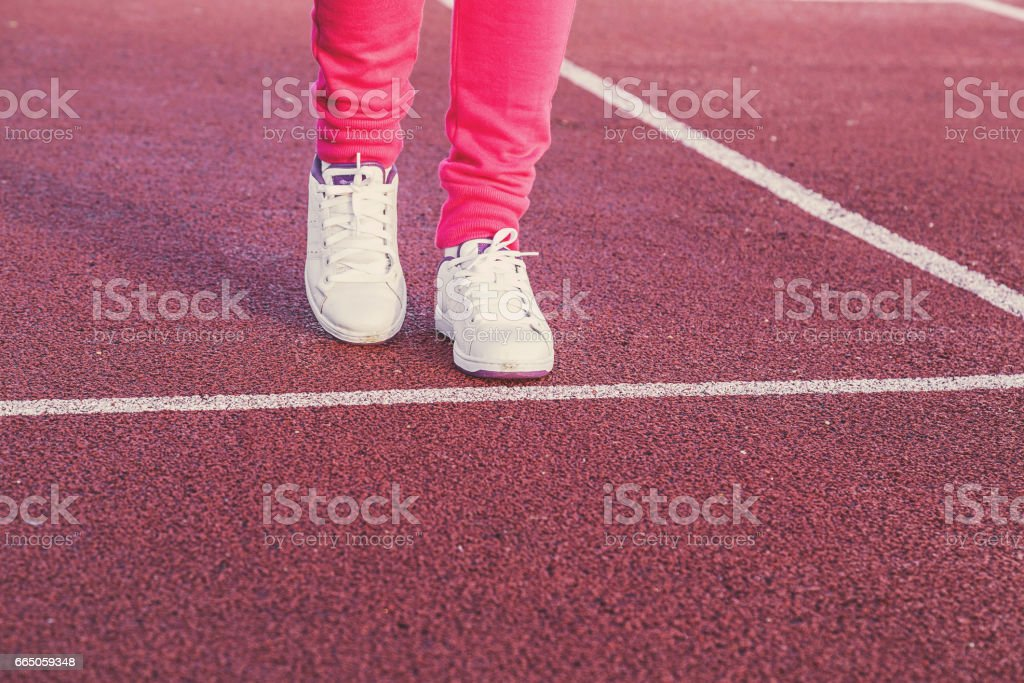 Woman running in the stadium in spring. Active lifestyle in the early morning. Sports shoes on the runway. stock photo