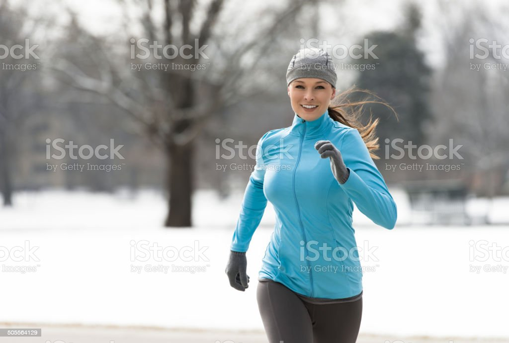 Woman Running in Winter stock photo