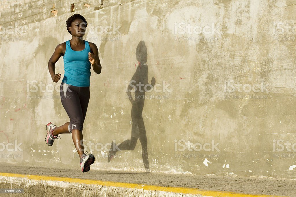 Woman running next to her shadow royalty-free stock photo
