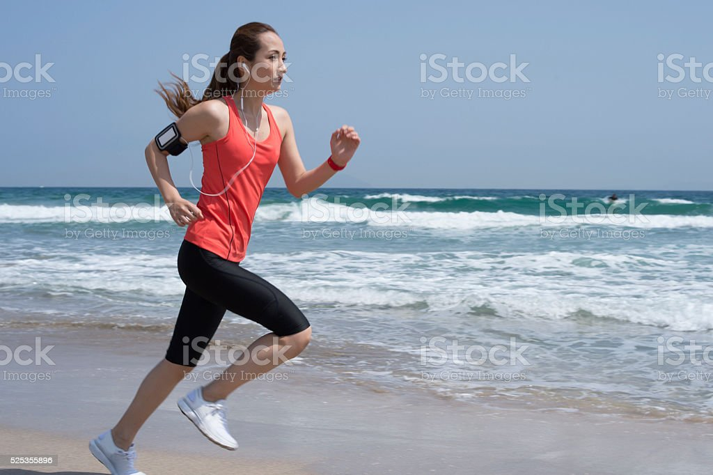 Woman running on beach in order to train leg strength stock photo