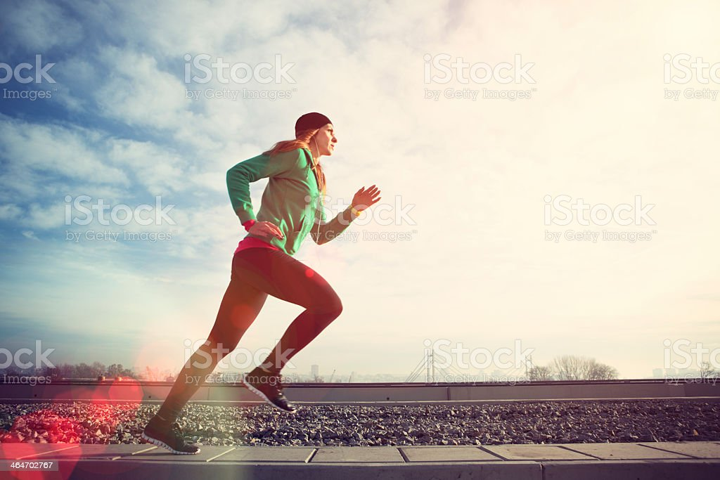 Woman running on bridge with cityscape behind royalty-free stock photo