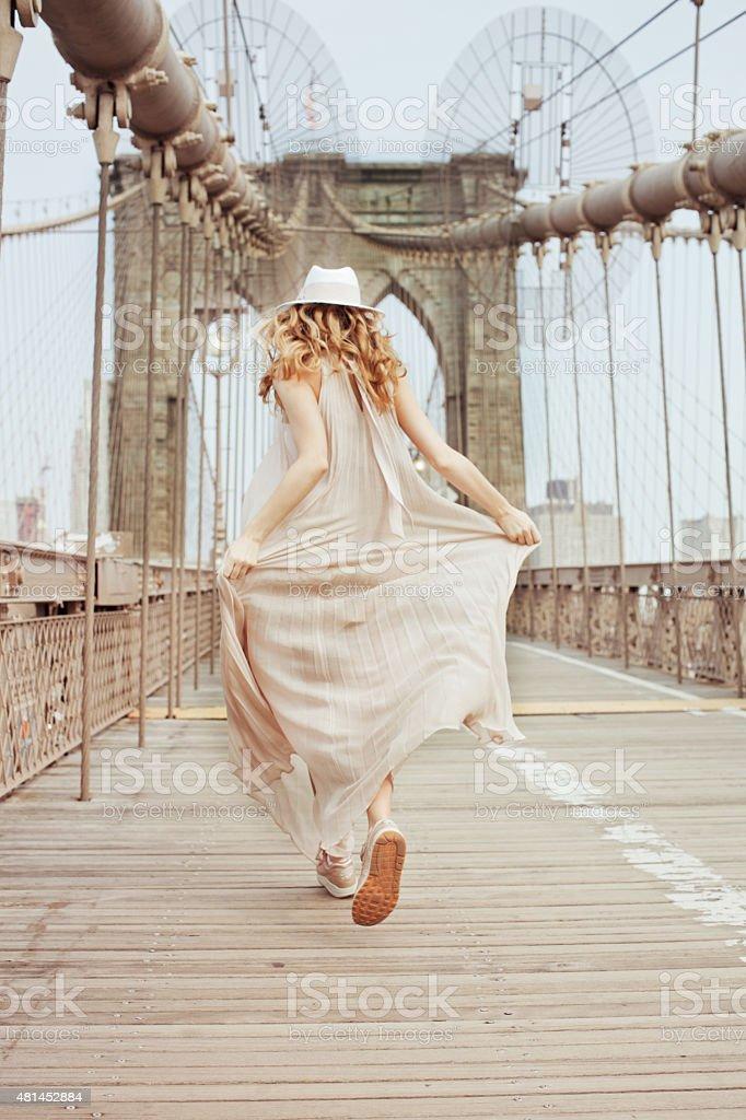 Woman running on Brooklyn Bridge stock photo