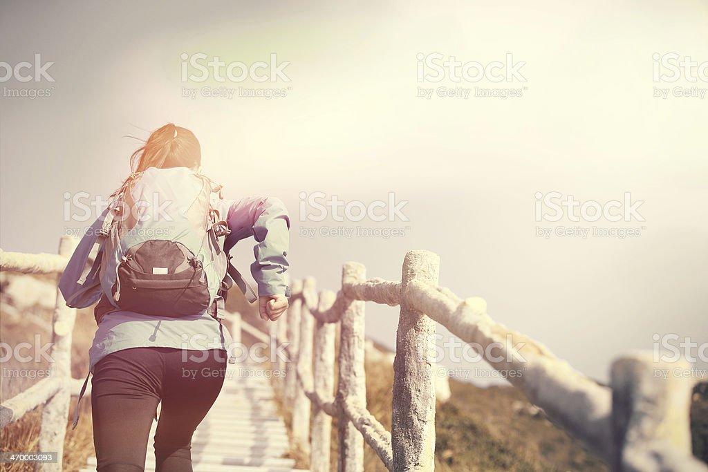 woman running on mountain stairs stock photo