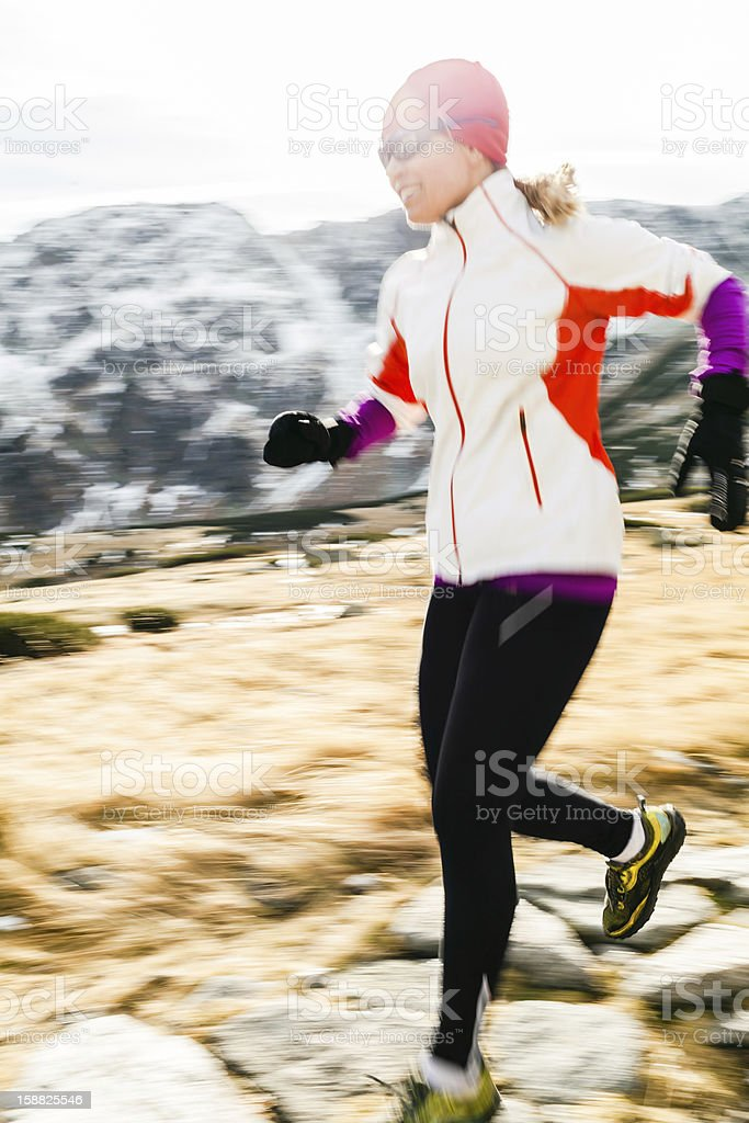 Woman running on mountain trail winter fall royalty-free stock photo