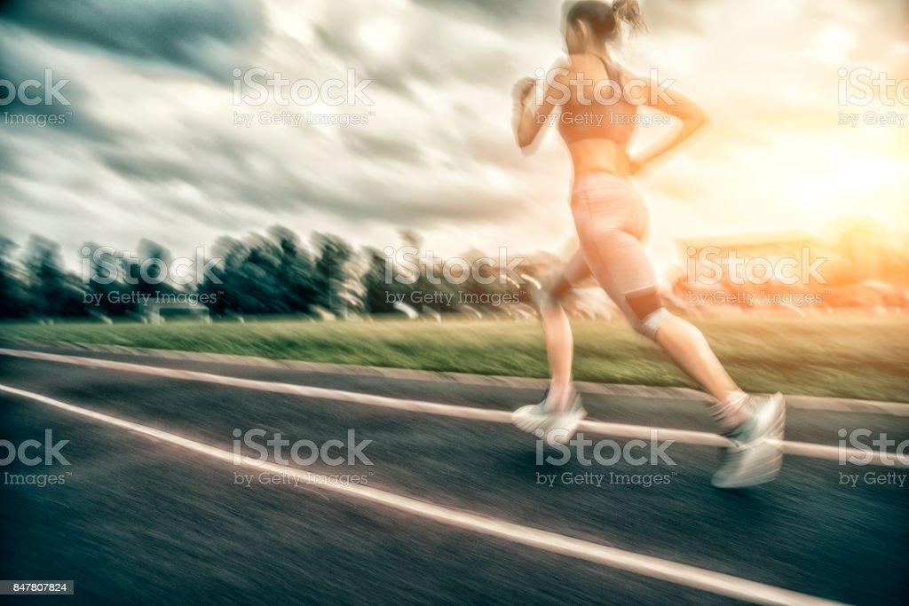 woman running on stadium track stock photo