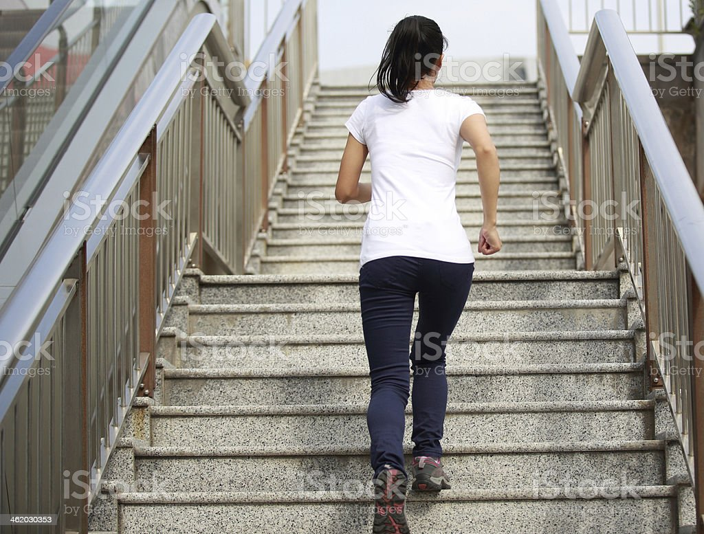 woman running on stone stairs stock photo