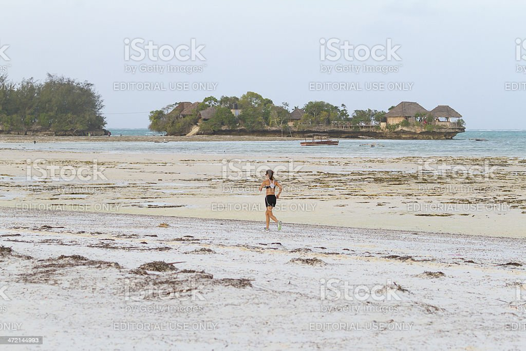 Woman running on the beach at low tide - Zanzibar stock photo