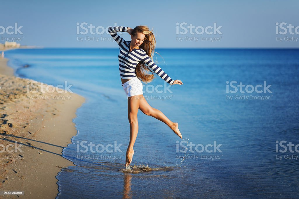 Woman running on the beach at sunset stock photo