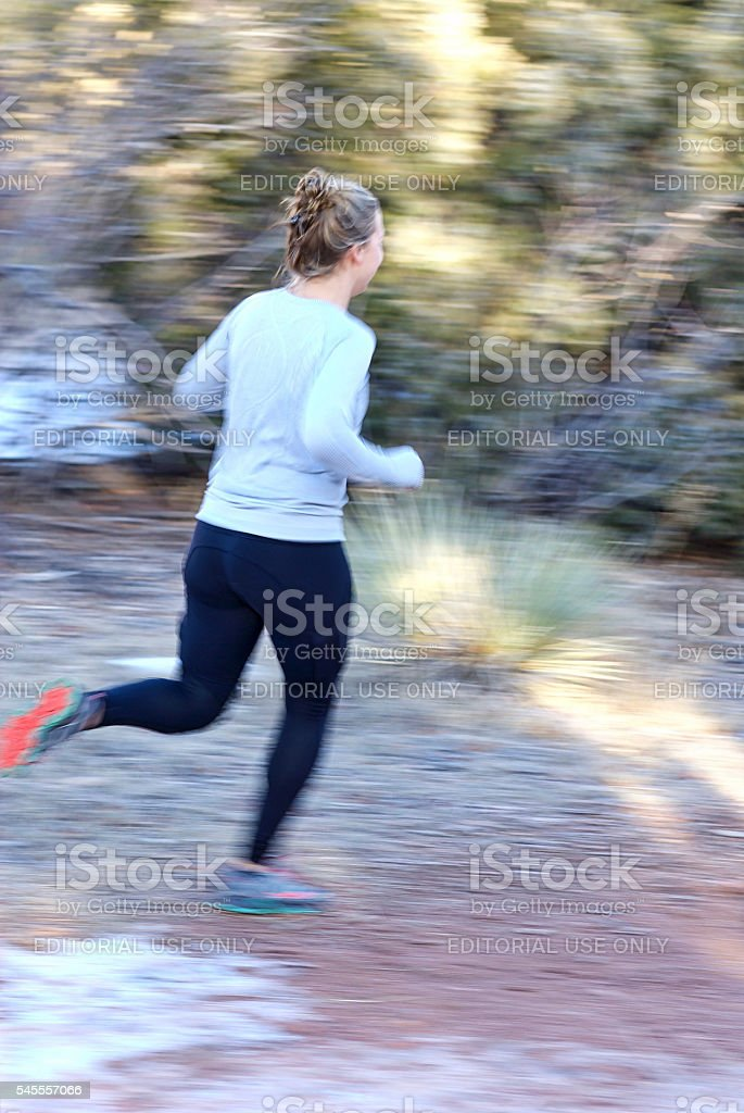 Woman running on trail in the woods stock photo