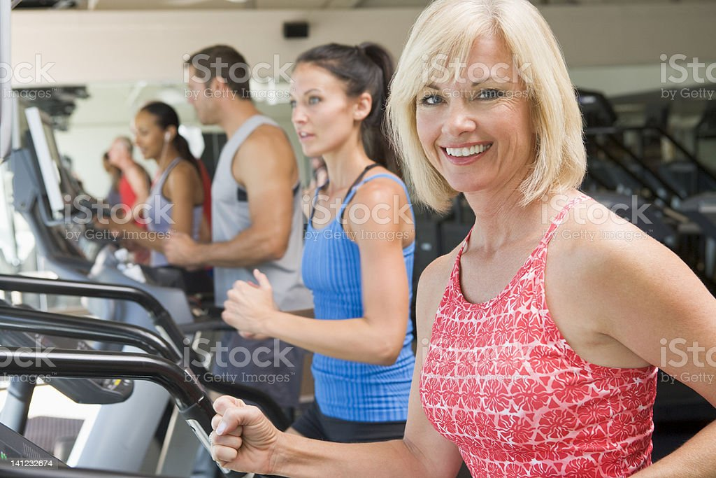Woman Running On Treadmill At Gym stock photo