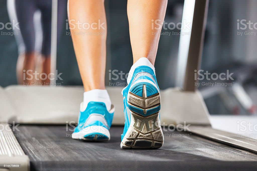 Woman running on treadmill in gym. stock photo