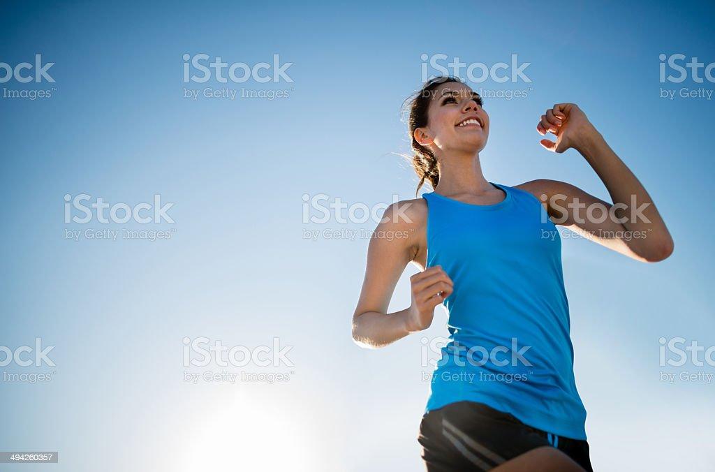 Woman running outdoors stock photo