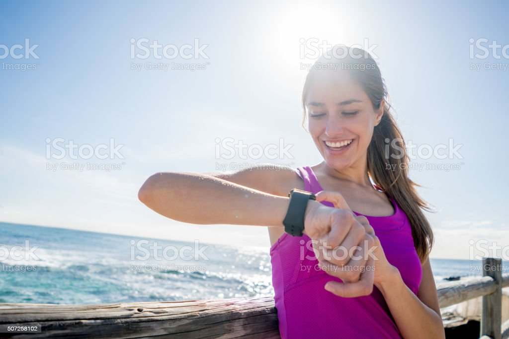 Woman running outdoors using a smart watch stock photo