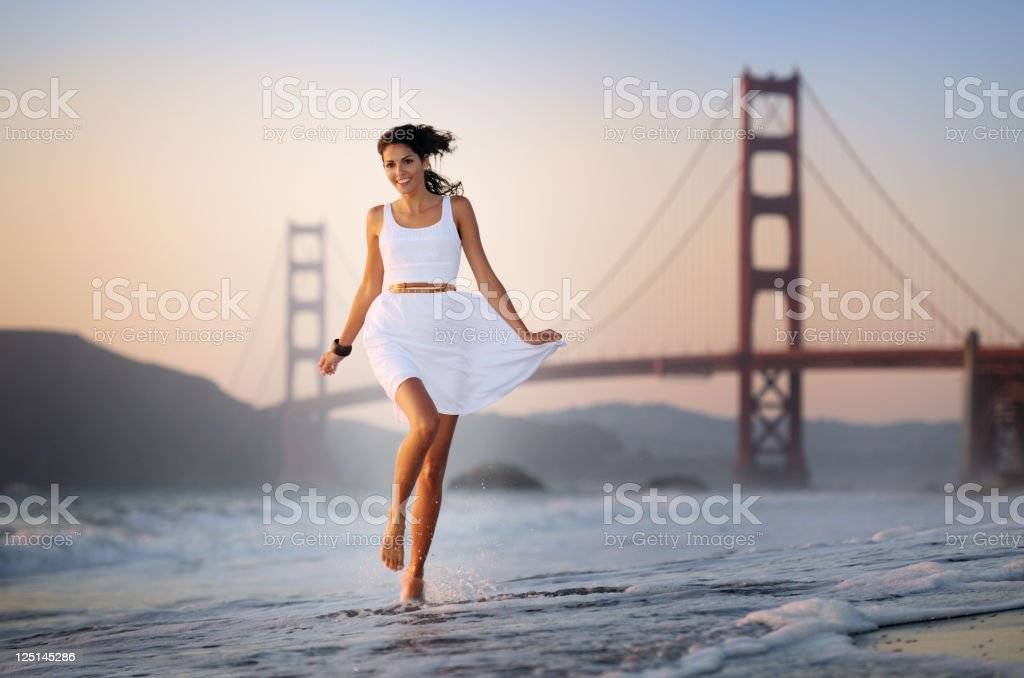 Woman running playful through the surf, Golden Gate Bridge (XXXL) stock photo