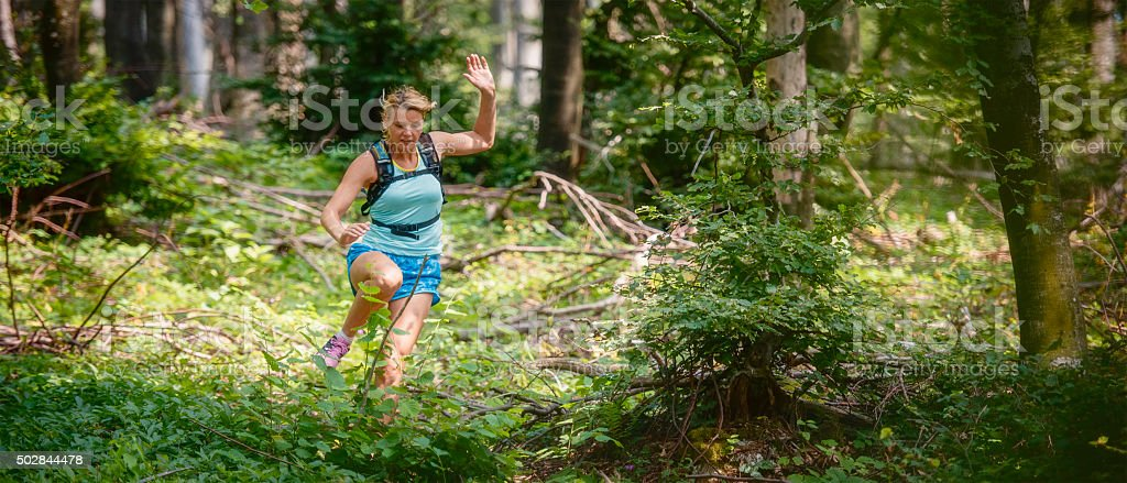 Woman running through a forest stock photo