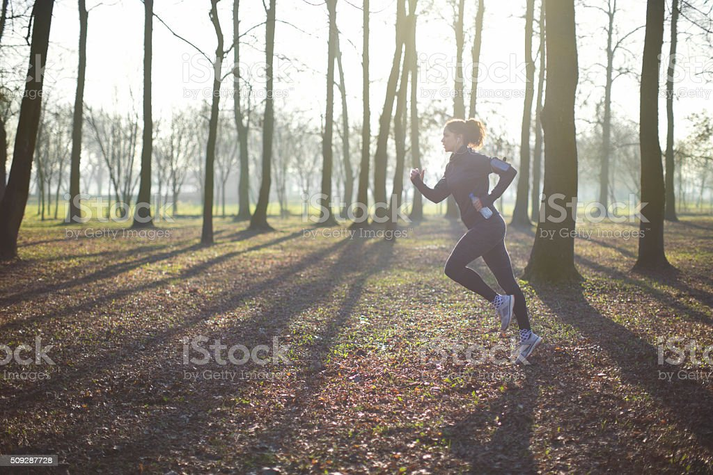 Woman running through forest stock photo