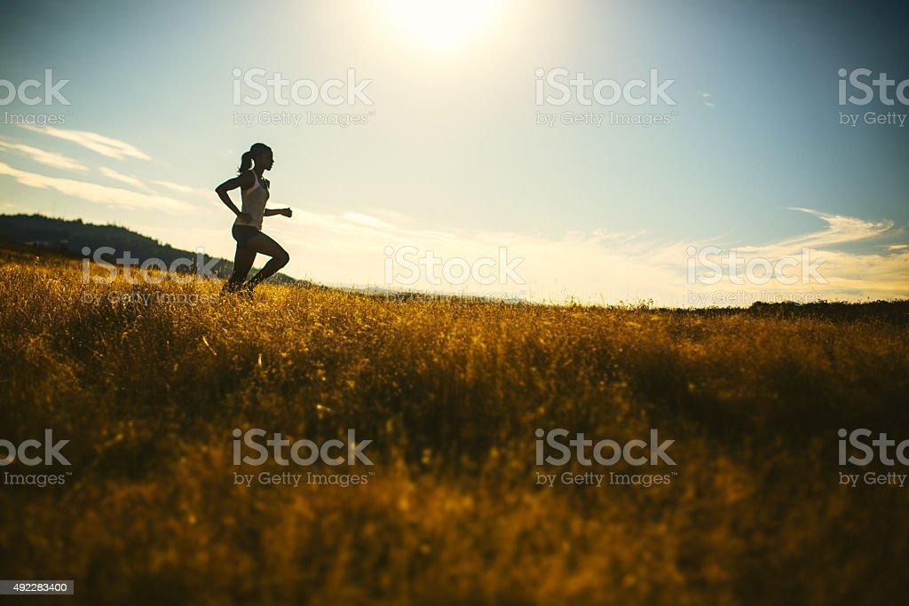 Woman Running Through Golden Field stock photo