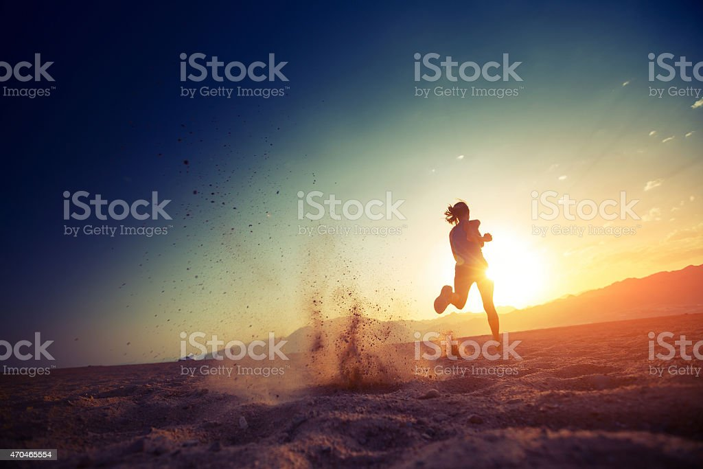 A woman running through sand at sunset stock photo