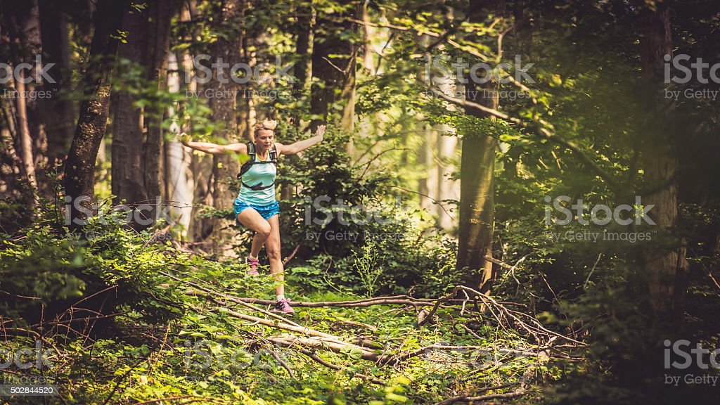 Woman running through thick undergrowth stock photo