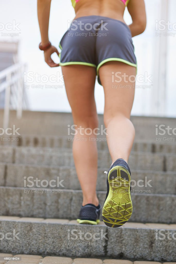 Woman running up on steps in the city stock photo