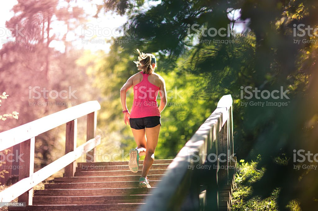 woman running up staircase stock photo