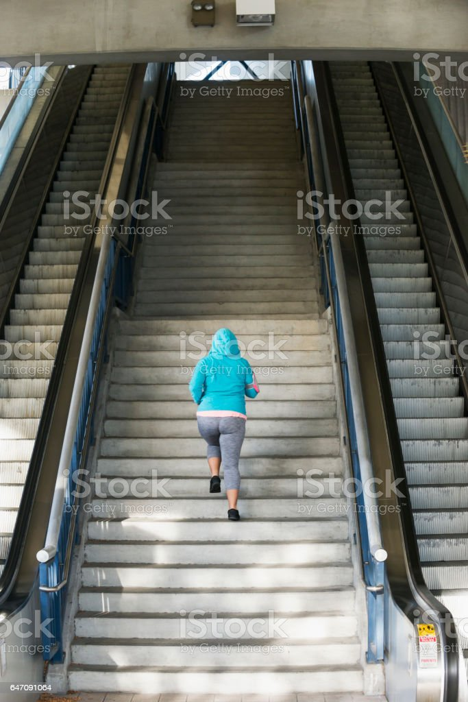 Woman running up steep staircase stock photo