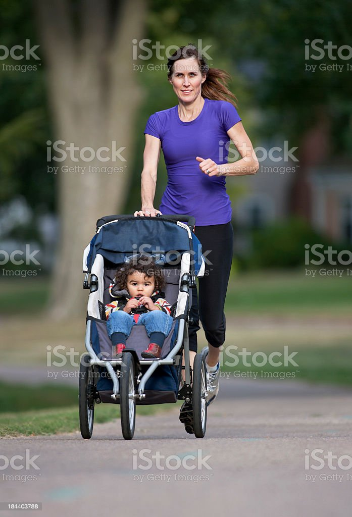 Woman running while pushing baby in stroller stock photo