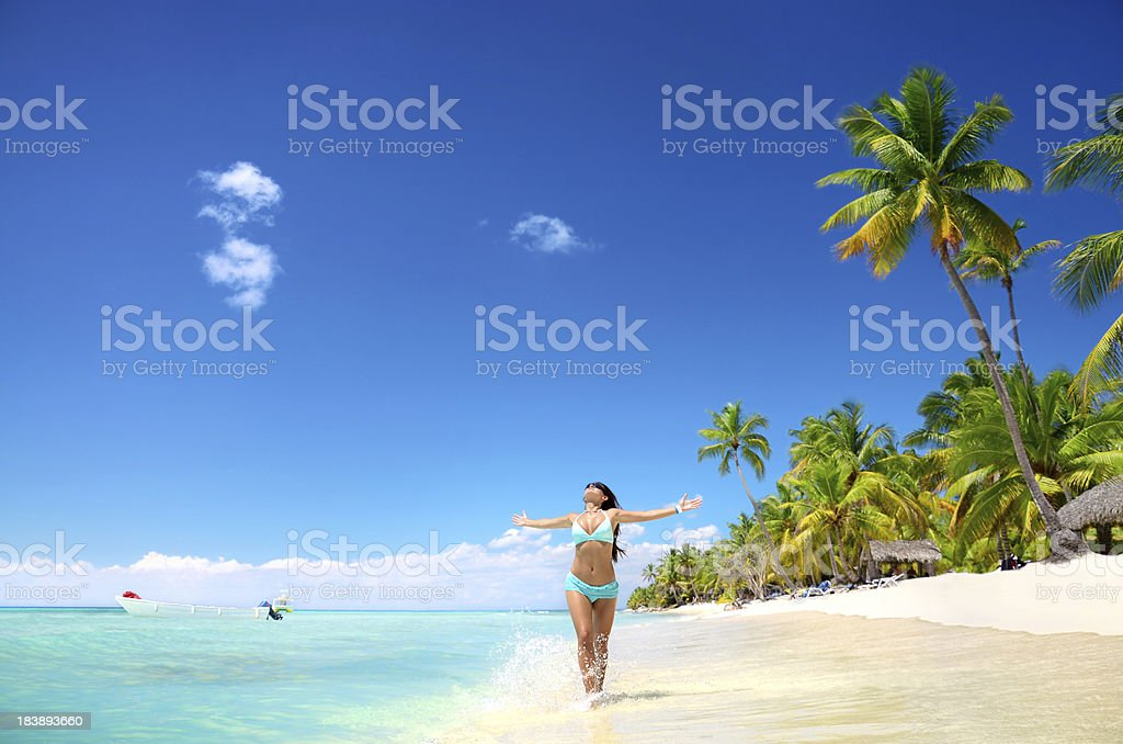 Woman running with hands out on tropical beach royalty-free stock photo