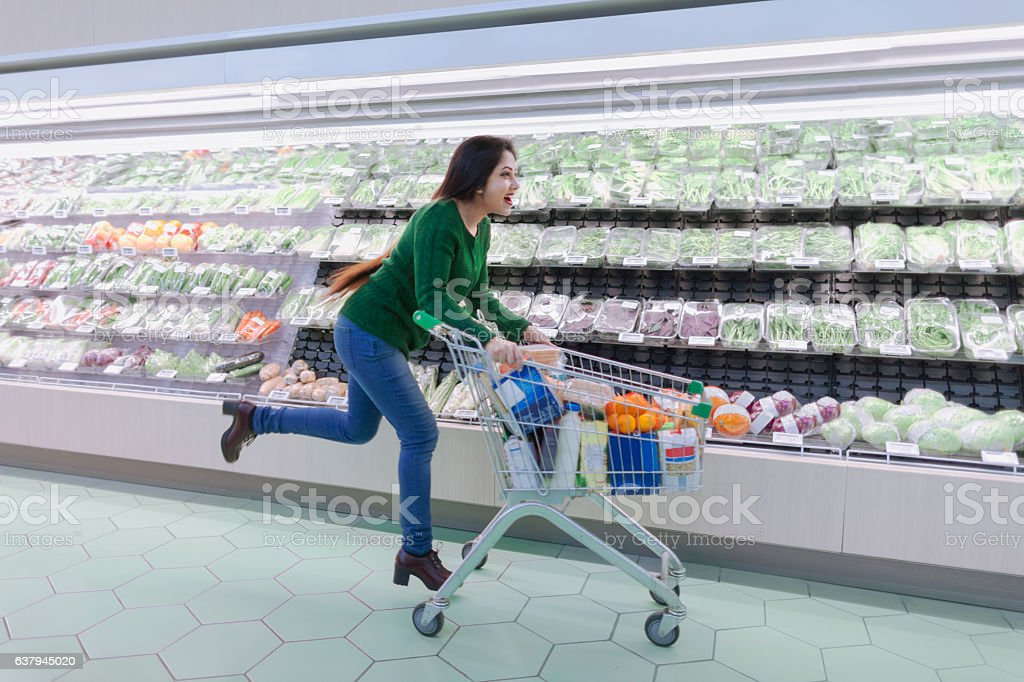Woman running with shopping cart in supermarket produce aisle stock photo
