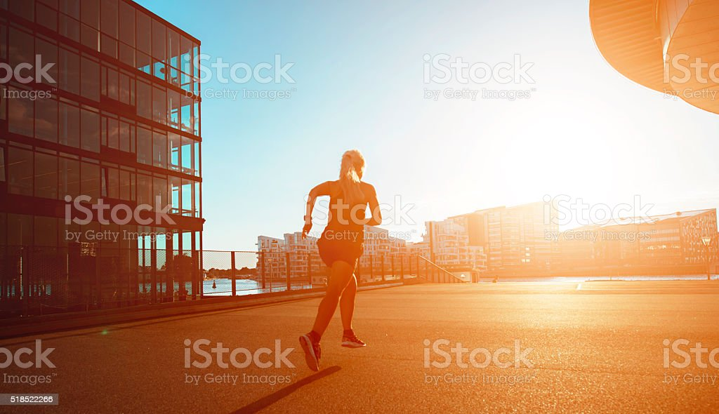 Woman runs towards sunset in the city stock photo