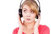 Woman sad girl in big headphones listening music