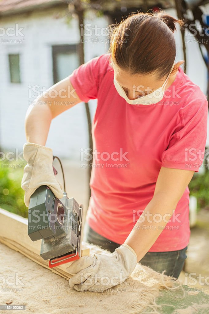 Woman sanding wood plank using electric sand machine stock photo