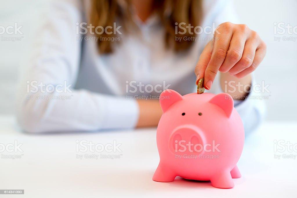 Woman saving money  - piggy bank stock photo