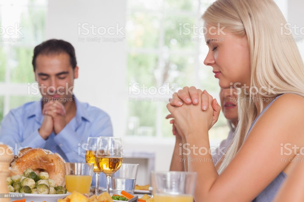 Woman saying grace with family before dinner stock photo