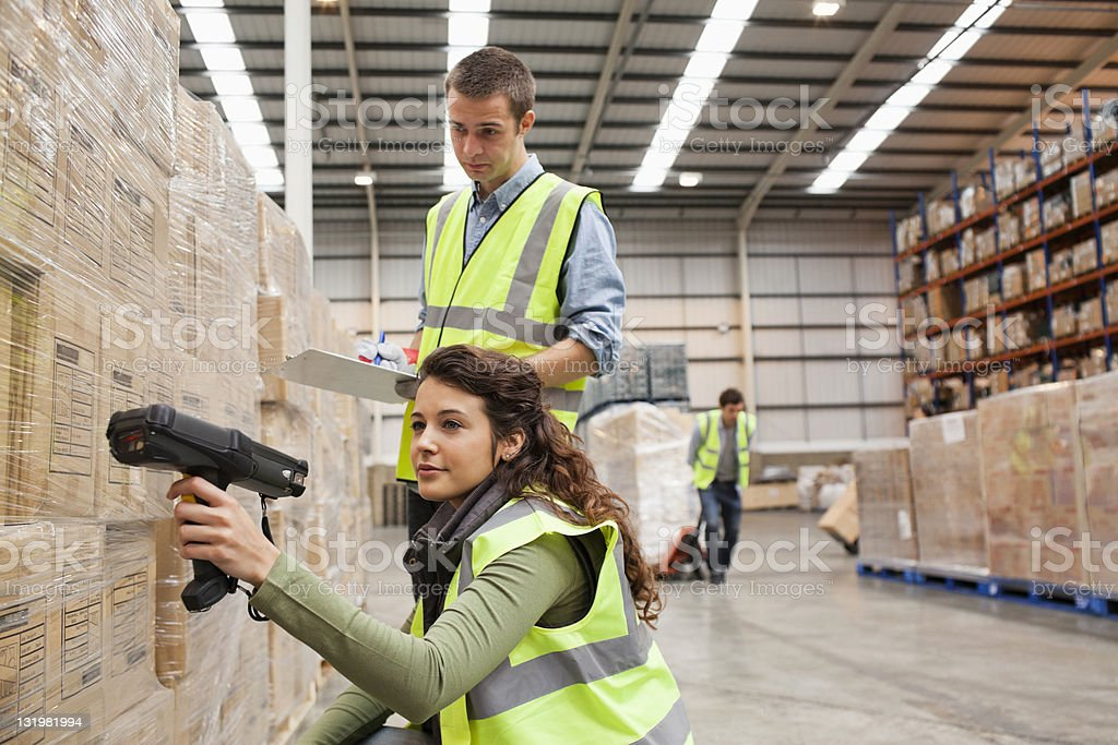 Woman scanning barcodes while young man with checklist stock photo
