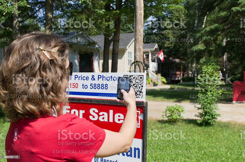 Woman Scanning QR Code on For Sale Sign stock photo